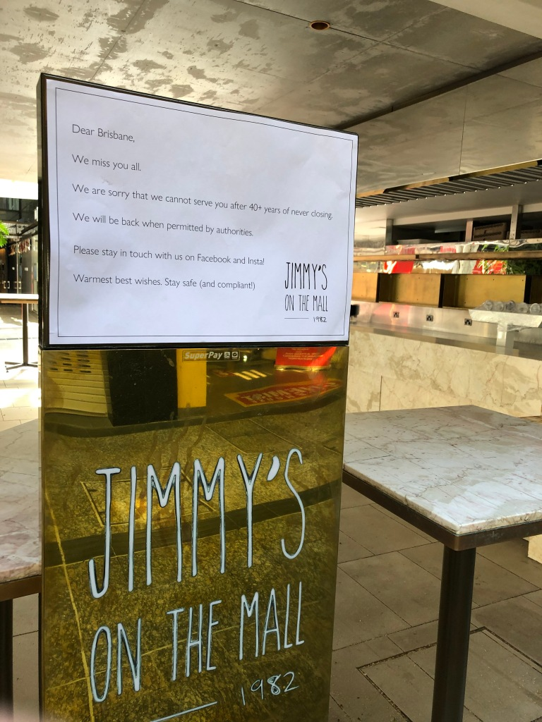 A photo taken during the time of Brisbane's first lockdown during April 2020 of a deserted Jimmy's on the Mall restaurant, with a sign saying they will be back when permitted by authorities.
